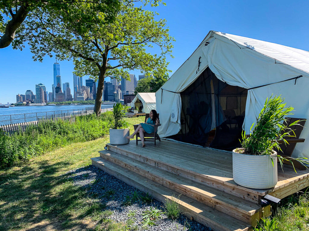 Sitting outside Journey Tent #14 while glamping on Governor's Island in New York City from Collective Retreats. Lower Manhattan and One World Trade Center is in the background.