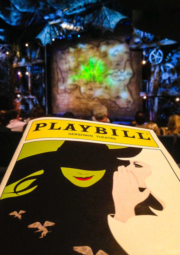 The Playbill for Wicked in front of the stage at The Gershwin Theater in New York City - From big, bright classic American musicals to intimidate plays to more experimental works. New York theatre is one of a kind and worth experiencing, even just once. These are my best tips for attending a Broadway show and for how to buy Broadway tickets.